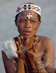 Africa | A Kung woman sings and claps her hands to the rhythm of her menfolk. The Kung are San hunter gatherers, often referred to as Bushmen. The Kung live in the harsh environment of a vast expanse of flat sand and bush scrub country straddling the Namibia Botswana border. | © John Warburton Lee