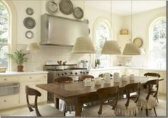 windows on both sides of stove and above sink, farmhouse table in kitchen