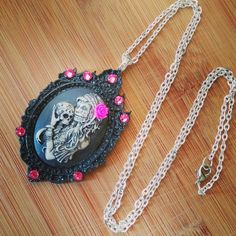 This new design is so gorgeous!  I've hand painted this 40x30mm Gypsy skeleton lady cameo in black paint to bring out the gorgeous details and shadowing. She wears a beautiful rose in her hair.  She's set in a decadent glossy black gothic frame and accented with swarovski crystal rhinestones.  Co...