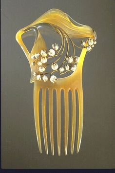 René Lalique. Comb. Lilies of the Valley 1900. Horn, gold, opaque enamel on gold. 6-1/8 x 3-3/4 inches