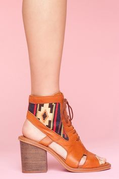 Amazing camel leather lace-up booties featuring southwest-inspired woven blanket inserts and cutout detailing. Open toe, stacked wooden heel. By Miista.