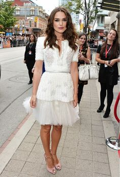 Keira Knightly is wearing a white cocktail dress with tulle hem and pink peep-toe heels.