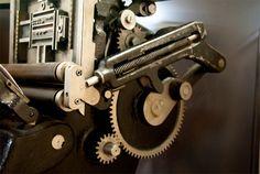 Detalle del muelle que presiona el cilindro entintador automático contra la forma que está montada en la máquina en el lado izquierdo de la fotografía.