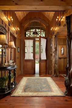Foyer: Luxe Lakefront Cabin in Tiger, Ga. | The foyer is a perfect example of how the cabin blends a thoroughly luxurious feel with charming rustic design. Polished tree trunk posts support the upper level, wrought-iron sconces light the welcome and all around gorgeous wood paneling wraps the space in warmth.