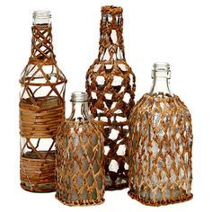 Bring a touch of organic-inspired appeal to your decor with this glass bottle set, showcasing eclectic silhouettes and artful woven rattan coverings.