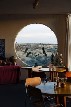 Crazy wonderful playfulness between the round window and the round tables in this restaurant dining room.