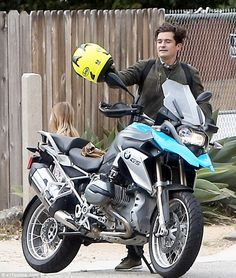 Cool: The handsome screen star was spotted mounting his beloved vehicle in a khaki green b...