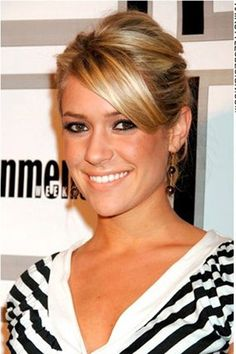 This is a chic hairstyle as Kristin Cavallari has her long hair styled up into a classy updo hairstyle. The hair is pulled back behind at the ears and lifted up at back. Long straight bangs are brushed across towards one side at the forehead.The hair is cut long.This hair colour is brown with blonde highlights.