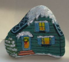 Sparkling snow accents a painted rock winter cottage.