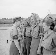 Lance Corporal E J Burck talking to German female prisoners of war during morning parade at a camp for SS, Luftwaffe and civilian women prisoners at Vilvoorde on the outskirts of Brussels.