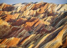 """Zhangye Danxia Landform Geological Park - Gansu Province, China  This zebra-like pattern in the mountains was created by different layers of red sandstone and other mineral deposits being compressed together over millions of years. The resulting """"layer cake"""" was then cleaved and buckled into its current position by the same tectonic plates responsible for creating parts of the Himalayan mountains."""