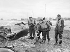 Four pilots of No 92 Squadron RAF based at Manston, Kent, pick through the wreckage of a Junkers Ju 87B, which they shot down while it was attempting to attack a convoy in the English Channel. The Squadron Commander, Squadron Leader J A Kent, who led the section, examines a fire extinguisher at far left.