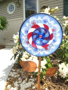 Glass plate flowers are garden art creations, made of vintage glass items. I love to repurposed lovely vintage glass, because there is still beauty in them to be enjoyed. I have used them to to create something new, a one of a kind work of art! The pieces are gathered at thrift stores, flea markets, yard sales, etc. They are designed to be displayed on a stake in your garden among your plants and flowers.  This garden art glass plate flower is comprised of vintage mid century glass, in the…