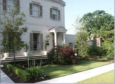 french country  house facade smooth white stucco and off white grey shutters, formal entree garden and pathways