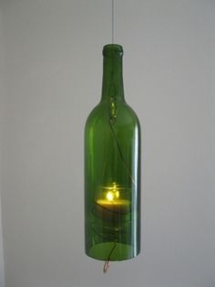 Hanging wine bottle candle, dark green. Made from recycled wine bottles and electrician's wire.#wine bottle candle, wine bottle votive, hanging wine bottle candle, recycled bottle, recycled wine bottle