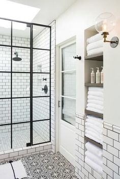 White and black bathroom boasts an alcove filled with shelves holding towels alongside a white and black floor in Cement Tile Shop Bordeaux Tiles. / I really like this!