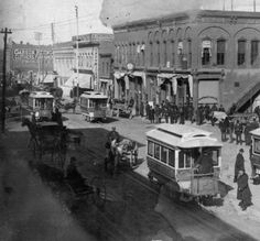 "~15th Street, Denver~1887 View of trolley cars on 15th Street at the intersection of Lawrence Street in downtown Denver, Colorado. Men stand beside commercial buildings; sit on horse-drawn wagons; or stand on trolley cars with numbers and lettering that read: ""7"" ""2"" ""5"" ""6"" ""E. Eighteenth St."" and ""Colfax Avenue."" Signs painted on multi-story brick buildings read: ""Garson, Kerngood & Co. Clothiers, Furnishers"" ""A. Jacobs & Co. Boy's Clothing"" and ""W.E. Stone Dentist"" on the McClelland…"