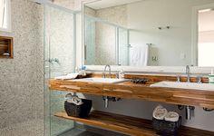 Para levar a natureza para dentro do banheiro de 7 m², a arquiteta Ana Karina Abud projetou o boxe com revestimento de seixos telados na cor areia. As duas pias ficam sobre a bancada de madeira teca