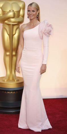 L'abito monospalla non è da tutte, specialmente se in una pallidissima tonalità di rosa. Eppure Gwyneth Paltrow lo ha scelto per gli Oscar, con tanto di maxi fiore sulla spalla coperta. Una silhouette a sirena che esalta la sua grazia!    #GwinethPaltrow #oscars2015 #oscar2015 #oscarsacademy