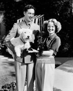 Actress Bette Davis and her husband Harmon Oscar Nelson, Jr pose outside with their dog in Los Angeles, California.