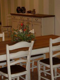 Tavolo allungabile all'estremo, realizzato in frassino con gambe a sciabola. Finitura bianco consumato con piano lastronato.
