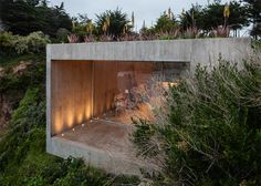 This concrete painting studio is half-submerged in the cliffside gardens of a house on the Chilean coastline