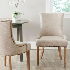 The Lester dining chair by Safavieh is full of elegant ease with low sloped arms and a slight hourglass shape to the seat back.