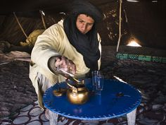 Akhmed pouring tea - made with with green tea, mint leaves, '44 spices' (none of which you can actually taste) and about as many sugars, near Merzouga, Morocco ©Simon Tupper