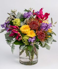 Vivid Blooms Arrangement A unique design of vivid yellows, purples and oranges - including roses, gloriosa lilies, and protea - are gathered in a gardeny design in our signature cylinder vase.