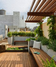 Water garden. Bring tranquility to an urban rooftop with the gentle burble of a fountain and let the traffic noise fade into the background. On this roof in New York City's East Village, a stream of water flows into a small pond, complete with water plants. Bench seating nearby is covered by a pergola, which will provide shade once the vines grow across it.