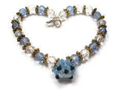 Charm Bracelet With Blue Beaded Bird by SmileykitCreations see this beaded bracelet at http://www.etsy.com/shop/smileykitcreations, $22.00