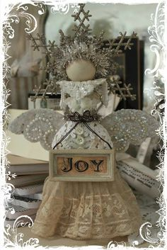 "The bottle is covered with lace and encaustic wax. The wings were made from an old cork coaster that I cut in half and then scalloped the edges. Then I covered it with glue and mica flakes and finally added the pearl embellishments. The head is an old round drawer pull with 2 glittered snowflake ornaments attached to back. A little ""vintage"" tinsel, some buttons and an old ornament and presto! bottle angel!!"
