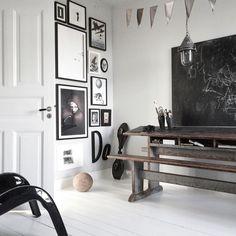 Fantastiskt vitt vardagsrum med målat trägolv, en gammal skolbänk samt en heltäckande fotovägg med bland annat inramade posters från printler.com, marknadplatsen för fotokonst. Inredning av bohemdeluxe @ instagram.