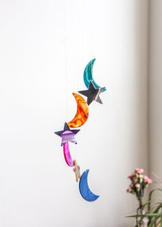 This gorgeous mobile is made with colorful polished agates in moon and star shapes, draping gracefully from a wooden ring. It is a perfect piece of outdoor deco