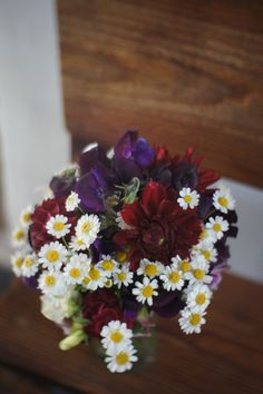 Burgundy flowers on a rustic wooden bench.