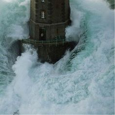 Lighthouse surrounded by huge waves
