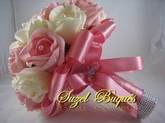 Lindo Buquê produzido com rosas super delicadas de e.v.a. em Rosa e Gelo, pétalas fininhas como uma pétala de rosa natural, aparência e textura super próximas às rosas naturais! <br> <br>Detalhes do Buquê: <br>*Aproximadamente 32 rosas grandes; <br>* Fitas de cetim envolvendo a haste; <br>* Laço duplo de cetim Rosa, super delicado. <br>* Strass no cabo. <br>* Meia - Pérola em todas as Flores. <br>* Borboletas na parte de trás do cabo. <br>* Flor de Strass no laço. <br>* Pontos de Luz de…
