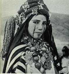 An Amazigh woman bedecked in jewellery and facial tattoos.