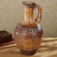 """Featuring an aged terra cotta finish and a band of geometric shapes, the Etruscan Urn will make a stunning addition to your home's decor. Ancient-looking ceramic urn has a handle and a circle and diamond pattern typical of the period. For decorative use only. Urn measures 10""""dia.x17""""H.    • Perfect decorative accent for anyone with an interest in antiquity  • Urn looks great alone or displaying your faux greenery"""