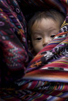 Niña envuelta en perrajes a tuto de su mamá en el mercado de Sololá