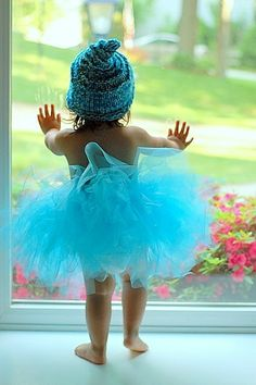 little girl in blue tutu and blue beanie looking outside