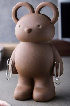 Beer schaar van Qualy. Schaar met een houder in de vorm van een beer. De handvatten van de beer vormen tegelijkertijd de oren van de beer. De bruine beer ziet er niet alleen lief uit, maar houdt ook jouw schaar vast tot je hem nodig hebt. Met magnetische handen, waar hij paperclips mee vast kan houden. De beer kan ook gebruikt worden als papiergewicht. De beer staat rechtop en de schaar trek je er aan de bovenkant uit; zijn oren zijn namelijk de hendels van de schaar.