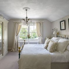 Neutral country bedroom with painted panelling and armoire