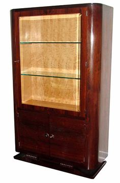 "This French art deco African rosewood vitrine with its blond sycamore interior dates from the 1930's. From its lap feet with scrolls to its nickel hardware to its beveled glass door it will display your prized possessions in the best of taste. The vitrine measures 65"" high x 34"" wide x 15"" deep."