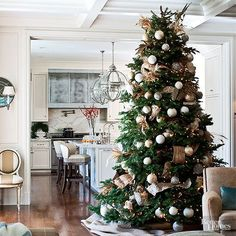Round ornaments, small string lights, and thick gold ribbon woven throughout give a giant tree a classic Christmas look. Choose decor that matches the room's color palette for a festive tree that isn't too invasive./