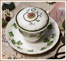 "The Victoria Sampler - Free Patterns  Teacup Pincushion  Designed by Thea Dueck  This design is inspired by my brand new ""Tea Party"" Sampler design which was released in July 2009.  Design area: 34h x 31w (2.1"" x 1.9"")"