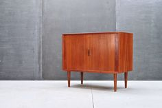 Denmark, c.1950s. Arne Vodder Teak Tambour Door Apartment Credenza. Very Good Vintage Condition, with some Uneven-ness to Varnish Remnants or Teak Oil. Wood Grain is Good, with Some Sun Fading to the Top Surface.    W: 36 x D: 18 x H: 30½ in.