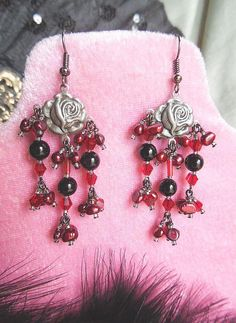 Alluring Victorian Goth Rose Chandelier Earrings! Created with gunmetal rose findings, I added clusters of deep wine potato pearls, red bicone crystals, and onyx beads. Red glass aurora borealis bugle beads are used at each center drop, and gunmetal glass seed beads are used as spacers. Dainty, yet stunning with lots of bling! Gunmetal steel ear wires complete this design. These earrings are one of a kind! Made with love and care to last!  Light and comfortable.  These earrings measure 2…