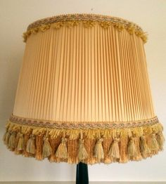 One of a pair of shades I restored. The style is a popular French or English shade type that started being produced in the 1870's and is still produced  in one form or another.   I covered mine in a period correct style.  A Pleated butter cream Dupioni silk With it's matching silk lining.  The trimming and matching tasseled trim are a complimentary tone of yellow with soft pink and green. The tassels hang in front of a gold silky fringe on the shade.