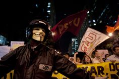 A protester wearing a Guy Fawkes mask joins a protest against the hike in bus and subway fares in Rio de Janeiro, Thursday, Brazil, June 13, 2013. Thousands of protesters are taking to the streets in Brazil's two biggest cities, protesting against 10-cent hikes in bus and subway fares. (AP Photo/Nicolas Tanner)